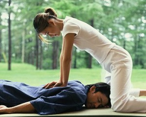 lady pressing down on the clients back in thai massage move